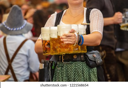 Oktoberfest, Munich, Germany. Woman waiter with traditional costume holding beers
