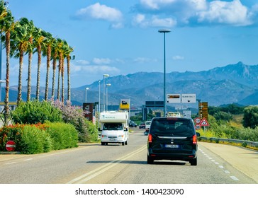 Olbia, Italy - September 11, 2017: Car minivan and Rv cavaran on the road in Costa Smeralda on Sardinia Island in Italy in summer. Motorhome rving on motorway. Camper trailer on highway. Palm trees