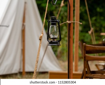 Old 1800s gas lantern hanging at the entrance of a canvas tent suggesting a civil war or gold rush camp in post-colonial america