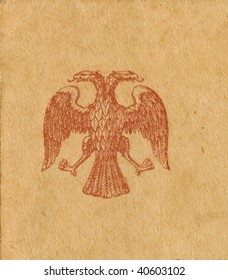 old 1900's double-headed eagle stamp on grungy postcard background. scanned object. original texture and color are preserved