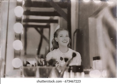 Old 1940s sepia photo of smiling young woman looking in theater mirror.