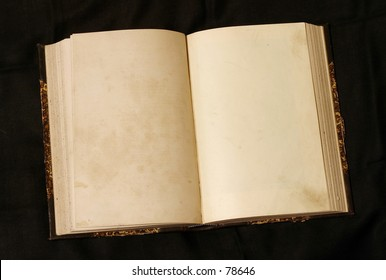 Old 19th century book open on both blank pages with stains and scratches.