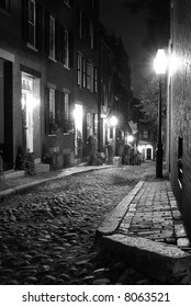 old 19th Century cobble stone road in Boston Massachusetts, lit only by the gas lamps revealing the shuttered windows and brightly lit doorways of the rowhouses on Acorn Street
