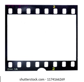 Old 35mm filmstrip or dia slide frame isolated on white background. Real analog film with signs of usage and dust.