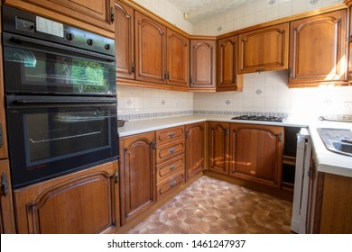 An old 80's style interior kitchen showing a classic brown British kitchen design typically used in the 1980's, with wooden kitchen cupboards.