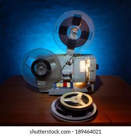 Old 8mm film projector in dusk beside a stack of film reels