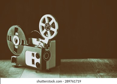 old 8mm Film Projector over wooden table and textured background