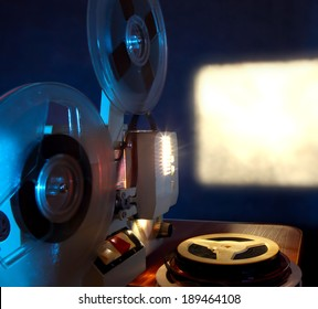 Old 8mm film projector showing the film in dusk onto a wall beside a stack of film reels