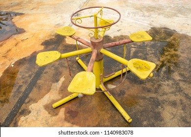 Old abandon rusty yellow merry-go-round in playground residential with circle wheel. On concrete floor