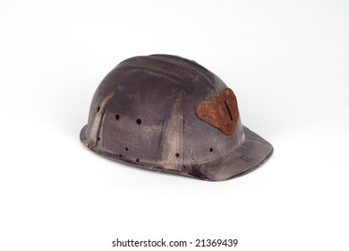 old abandoned bakelite helmet of a miner with rusted light-plug isolated on white