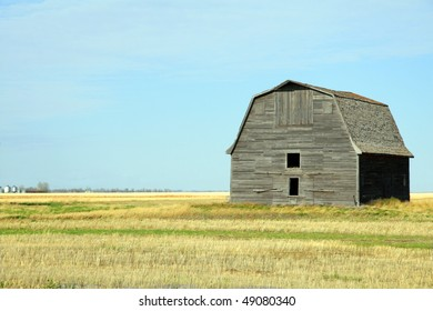 old abandoned barn against clear blue prairie sky