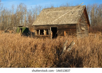 An old abandoned barn in a field of dry grass and weeds,  Image taken in the morning in fall