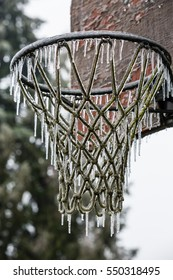 Old, abandoned basketball hoop and net frozen in an ice storm.  Focus is solely on the hoop while the backboard is intentionally blurred.  Large icicles hang from the net.