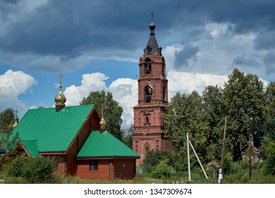 Old abandoned bell tower against the blue sky. In the foreground is a new Christian Orthodox Church with Golden domes. The bell tower is built of red brick. Church in rural or rural areas.