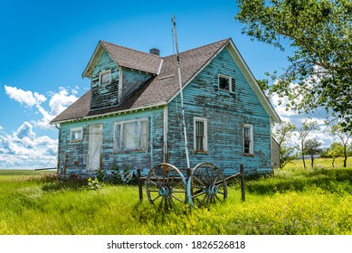 Old, abandoned blue prairie farmhouse with trees, grass, blue sky and a wagon wheel in Kayville, Saskatchewan, Canada