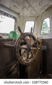Old abandoned boat, steering wheel from brass and wood. Ship rudder. Sailboat helm