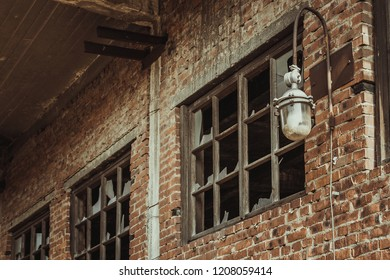 Old abandoned building bricks wall with broken windows and old electric lantern