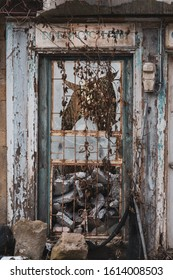 Old abandoned building with broken and peeled doors and window. Weathered wooden door looking creepy. English translation:
