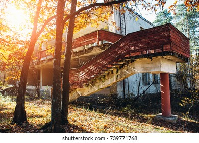 old abandoned building with stairs, autumn trees with sunny warm light, autumn warmth concept