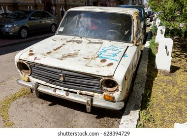An old abandoned car on city street. Rusty, worn-out old unnecessary design machine of  20th century rusts at  curb of  city street in poor, depressed quarter city