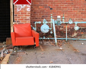 An old abandoned chair in a city alley