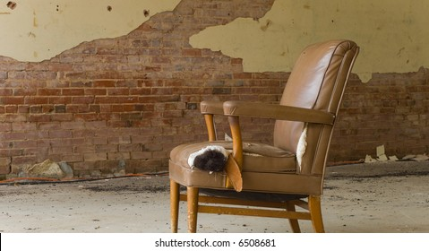 An old abandoned chair left in an abandoned delapidated building.  Interesting how the colors of the building and the chair match- space for copy