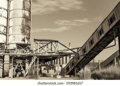Old, abandoned concrete plant with iron rusty tanks and metal structures. The crisis, the fall of the economy, stop production capacity led to the collapse. Global catastrophe. Old photo effect.