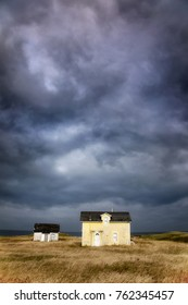 Old abandoned fishermanâ??s cottage and outbuilding with dramatic storm clouds. Havre Abert, Ilse de la Madeleine, otherwise known as the Magdalen Islands, Canada