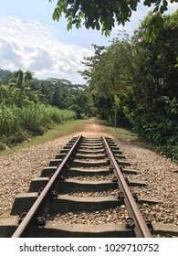 An old abandoned disused railway train line with iron track and sleepers still intact.