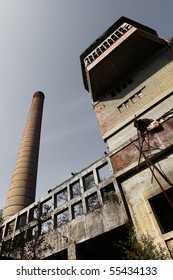 Old and abandoned factory and chimney with gray sky above