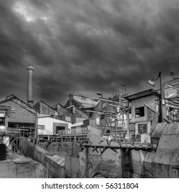 Old abandoned factory with dramatic clouds in sky.