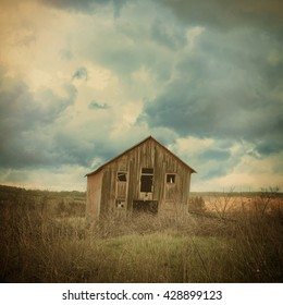 An old abandoned farm house is in the country with scary clouds in a field for a destruction, barn or scary concept.