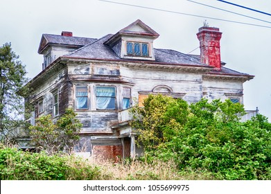 old abandoned farm house with overgrown bushes