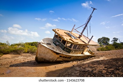 Old abandoned fishing boat decaying on land, left to rust discarded on beach in Queensland, Australia.