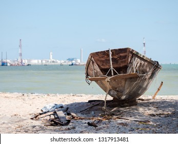 Old, abandoned fishing boat on the beach with a growing industrial estate in the background in Map Ta Phut, Rayong Province in Thailand