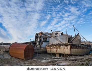 Old abandoned fishing boats near the harbor in Gustavus Alaska with dramatic cirrus clouds.