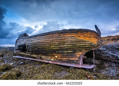 An old abandoned fishing vessel from the early 1900's rests on a remote beach as it rots, exposing the ship's wooden ribs and hull infrastructure.