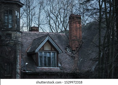 Old abandoned gothic house. The ruined mansion stands in park. Mysterious window. Gothic background. Halloween party place. Scary house. Window and roof of old palace. Frightening medieval building
