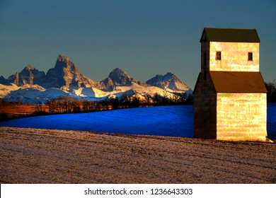 Old abandoned grainary grainery building with snow and Tetons Teton mountains in background