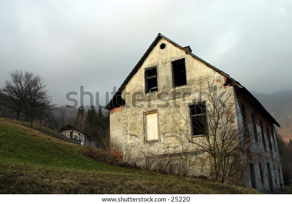 old abandoned house against the dark cloudy sky