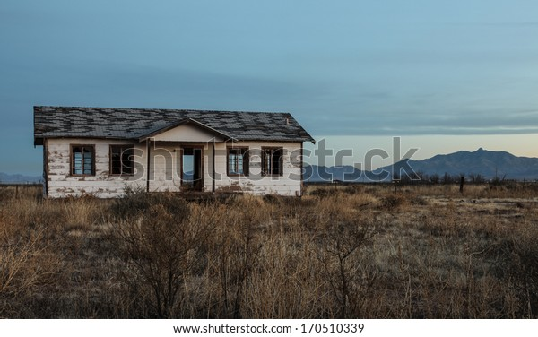An old, abandoned house built of weather-worn boards and shingle roof stands alone and open amidst semi-desert vegetation/See Through/Old, empty, abandoned house still stands, but now open to weather