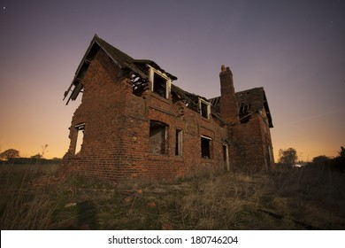 old abandoned house at night with star trails