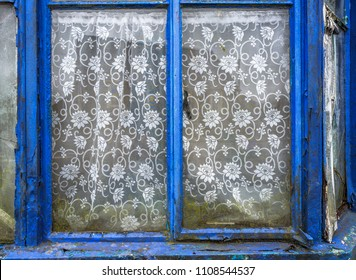 Old abandoned house with weathered window frames and net curtains.