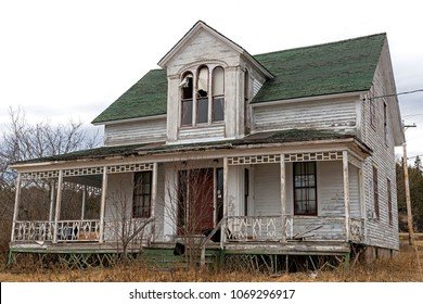 An old, abandoned house. Windows at the top are broken, the paint is peeling, and the front porch os falling down. Overcast sky.