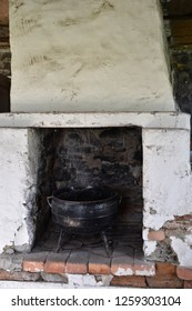 Old abandoned indoors fireplace with an old iron pot
