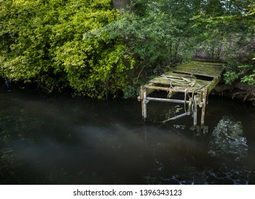 Old abandoned jetty along water.