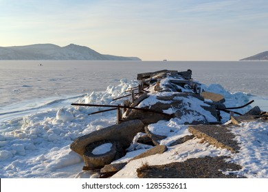 Old abandoned jetty in the bay Nagaeva. Away on the horizon the ship and the mountains. The sea is covered with ice. On ice a man and dogs. Cold winter weather. Magadan, Far of East Russia.