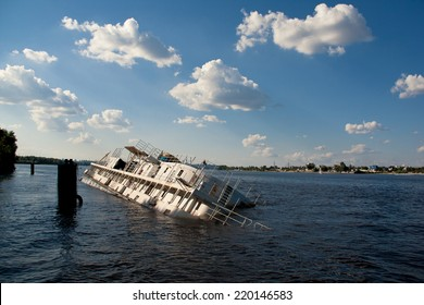 Old and abandoned passenger boat with damaged hull tied at dock half sinking in water