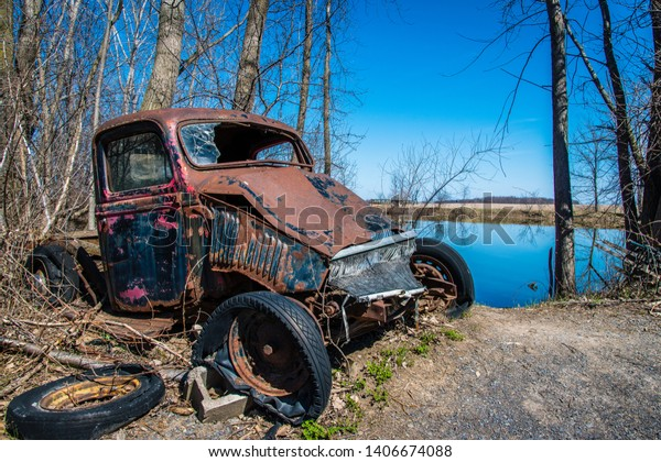 An old abandoned pickup truck near a small pond surrounded by trees
