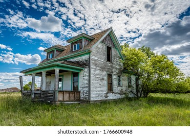 Old, abandoned, prairie farmhouse with trees, grass and blue sky in Saskatchewan, Canada